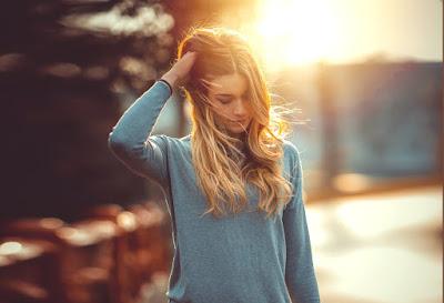 Chica rubia con blusa gris por las calles son sol de fondo