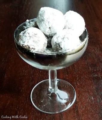 old fashioned champagne glass full of powdered sugar coated rum balls