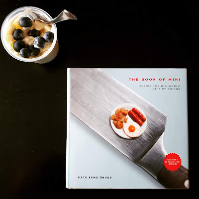 Book titled The book of mini next to a container of rice pudding and blueberries.