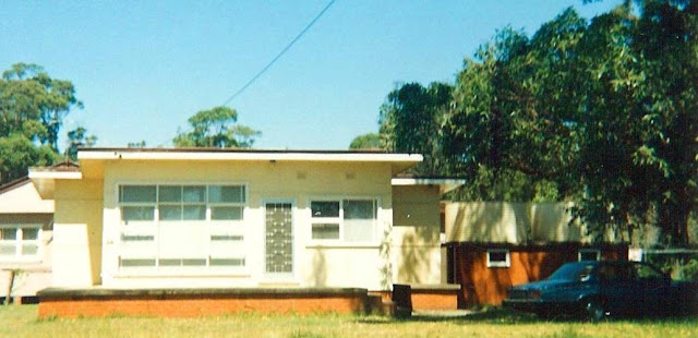 A 1950s style fibro home with yellow walls, white windows and trim and red brick foundations and tank stand. a grey car is parked in the front right.