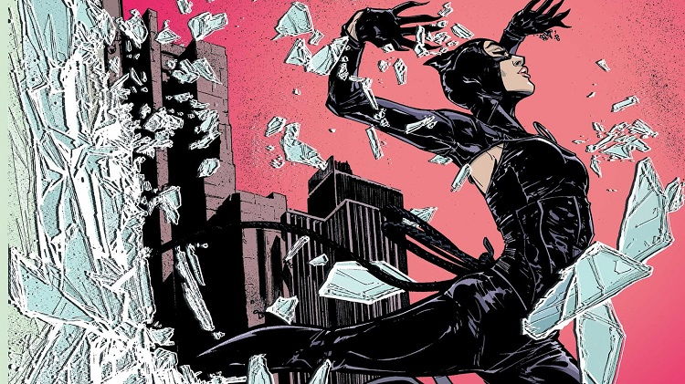 Catwoman arcs through the air in front of a pink and grey skyline, broken glass from an appartment window flying all around her