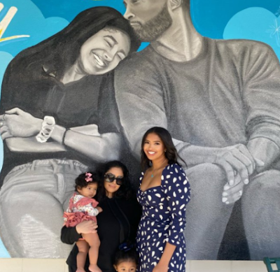 Late Kobe Bryant wife and daughters pose behind late husband and daugther picture