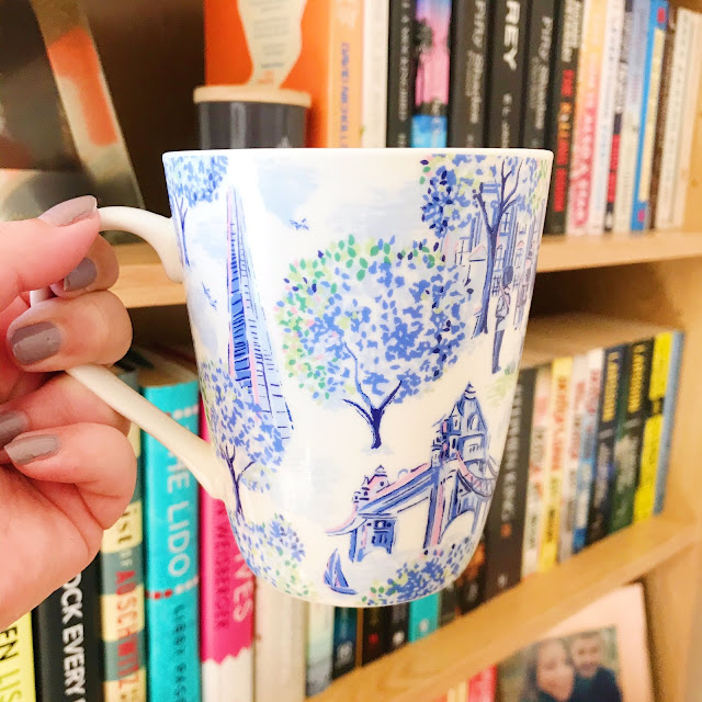 Cath Kidston mug held up in front of bookshelf