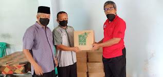 Ketua SMSI Sumbar Zulnadi, SH didampingi Sekretaris Gusfen Khairul menyerahkan paket sembako kepada Wakil Bendahara, Lailatul Aidil. (Ist)