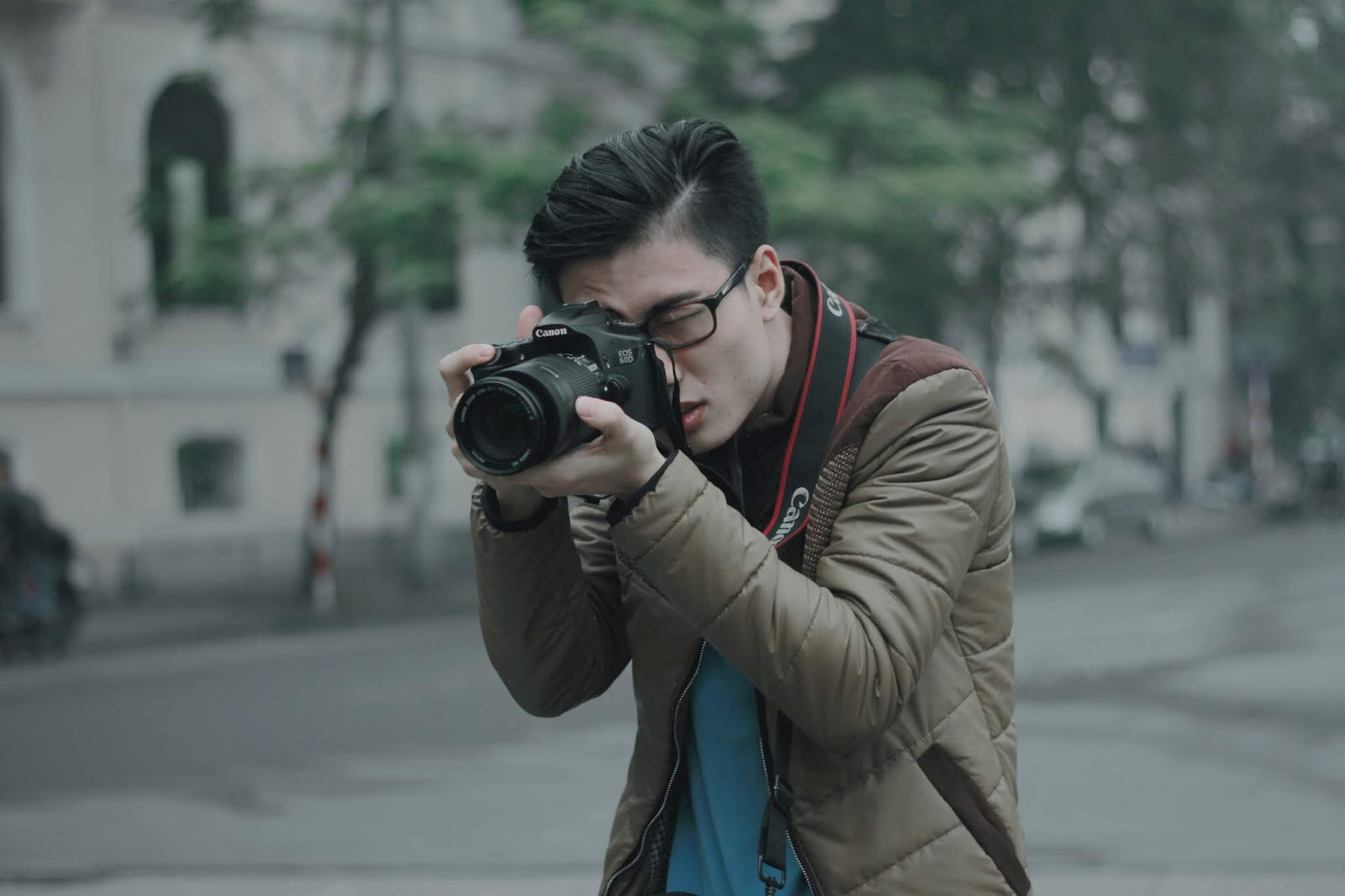 young man faces the camera. he has a camera and is taking a picture of something off-screen for blog post about war journalism movies