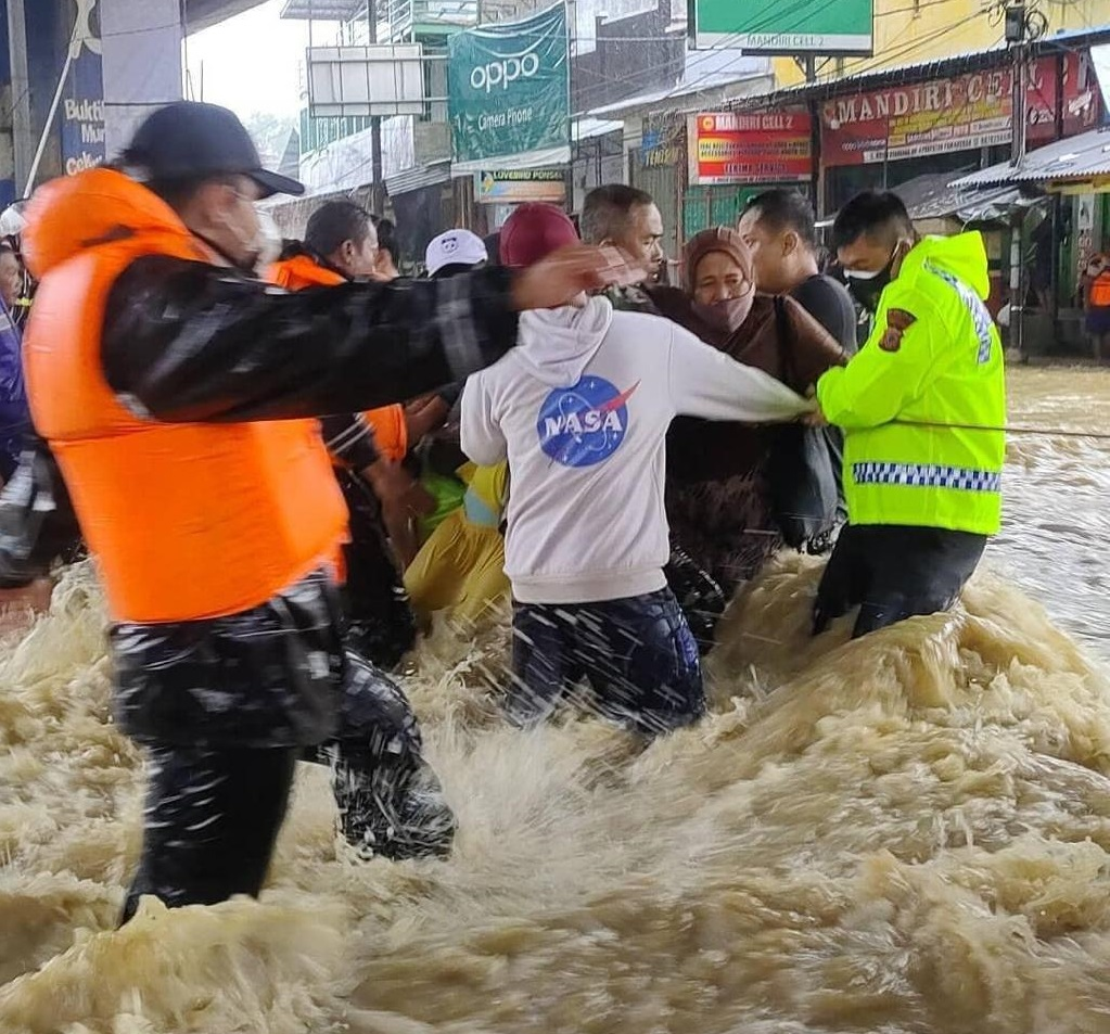 Petugas membantu warga melintasi arus deras di jalur Pantura Pamanukan, Kabupaten Subang. Foto: Ist