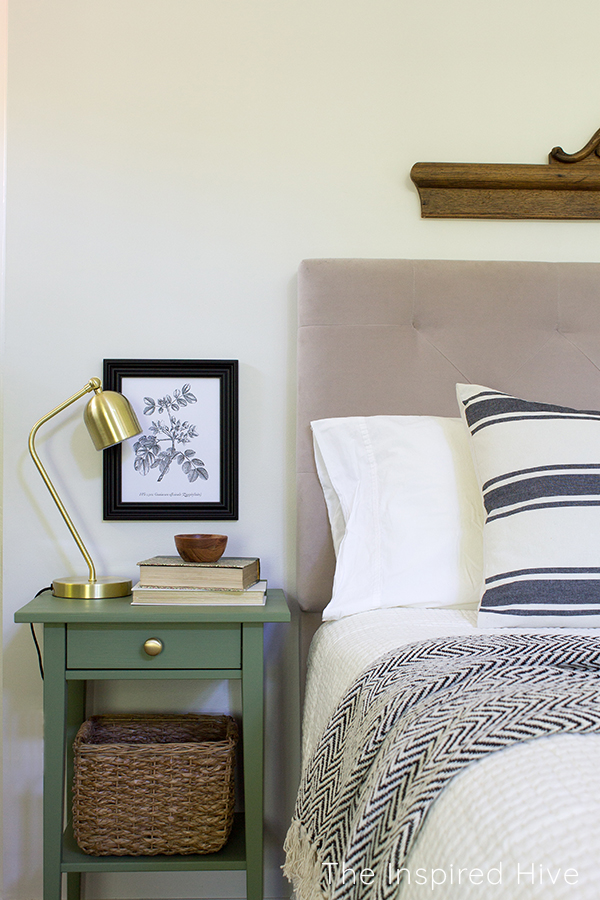 Master bedroom with green painted nightstand and brass task lamp