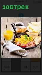 На столе приготовлен завтрак из тарелки с салатом и напиток в стакане, приборы завернуты в салфетку