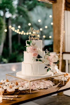 traditional wedding cake and cupcakes with flowers