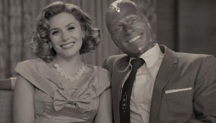 Mulher branca com cabelo chanel estilo anos 50 com vestido também estilo anos 50 que está sorrindo e olhando para frente, está sentada no sofá e ao lado dela está um homem robótico meio máquina usando um terno. Ele também sorri e a imagem é preto e branco.