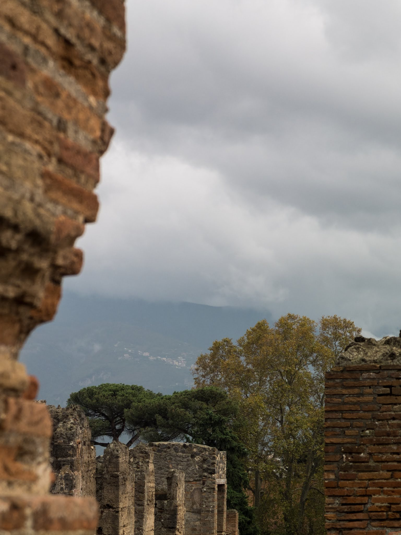Pompeii in the autumn surrounded with ancient brick walls, evergreens, golden maple trees and Mount Vesuvius.