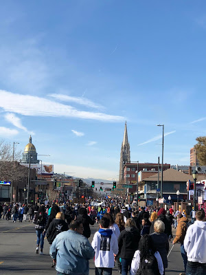 MLK 2020, CCB marching West, toward the State Capital and mountains. Gold dome of state capital on left and cathedral on right.