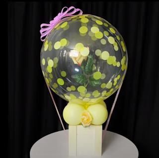 Transparenter Luftballon mit Rose befüllt.
