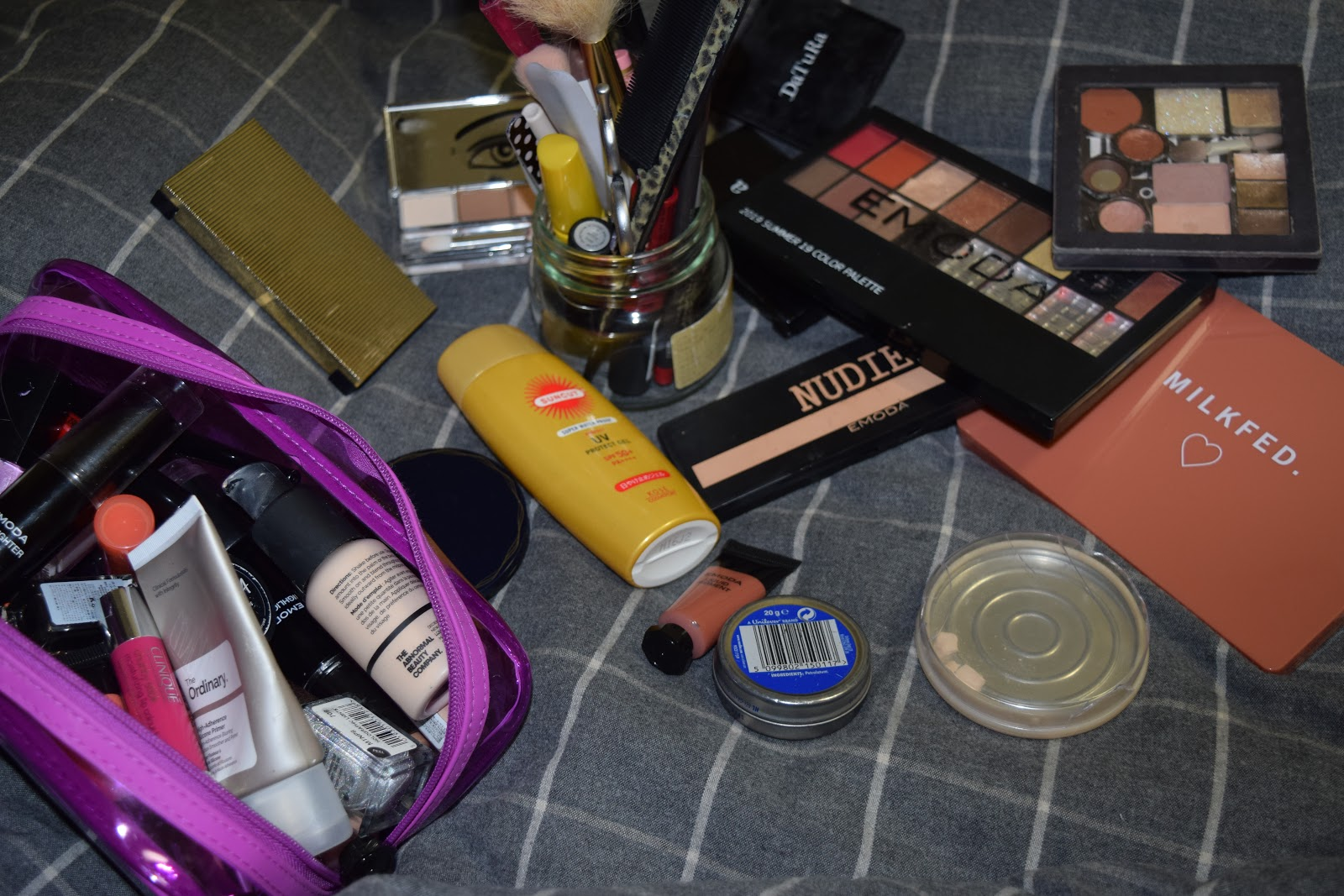 my makeup collection- palettes, a jar full of pencils and tools, a pouch full of lip products and