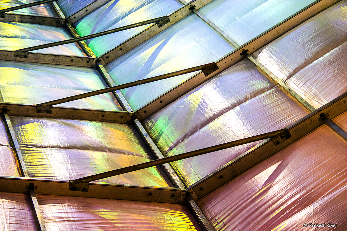 A Minimalist Photo of Steel bars and multicolored cloth of a temporary roof structure.