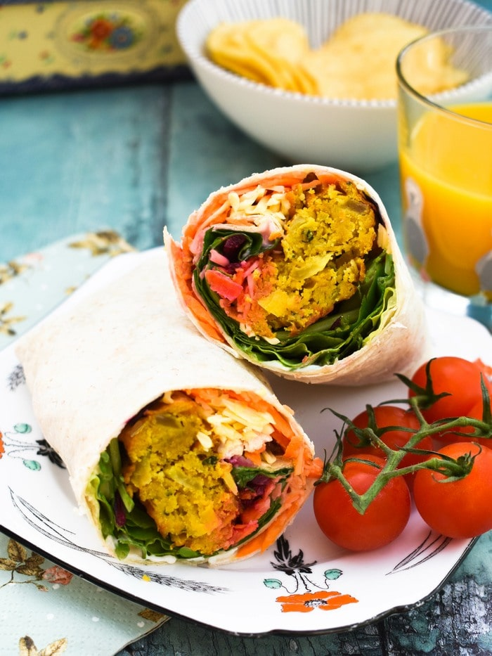An onion bhaji wrap cut in half on a plate, serve with an apple, crisps and orange juice