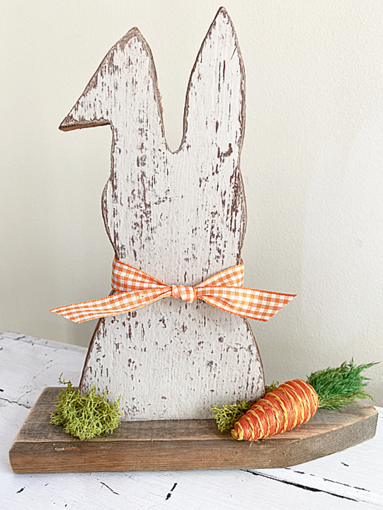 chippy Easter bunny on a picket fence with carrot and gingham bow