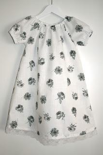 79905342 Hvit kjole med rosemønster. Stoffet er tynn bomull, og passer fint til  varme sommerdager. Hvit blondekant nederst.