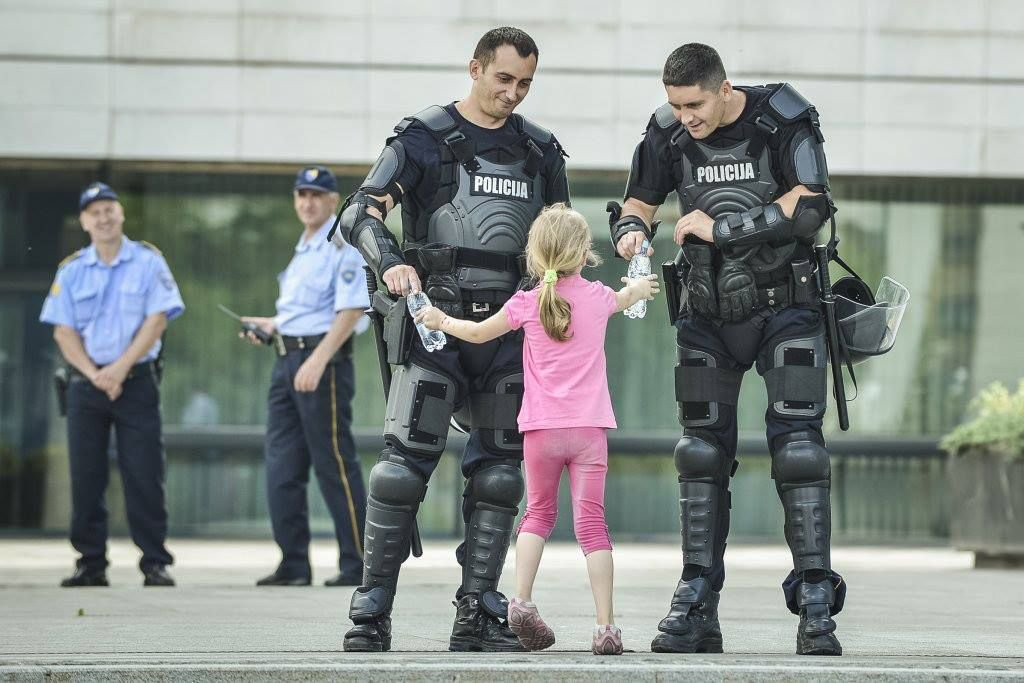 A young girl shares a bottle of water to Bosnian police. Bosnia.