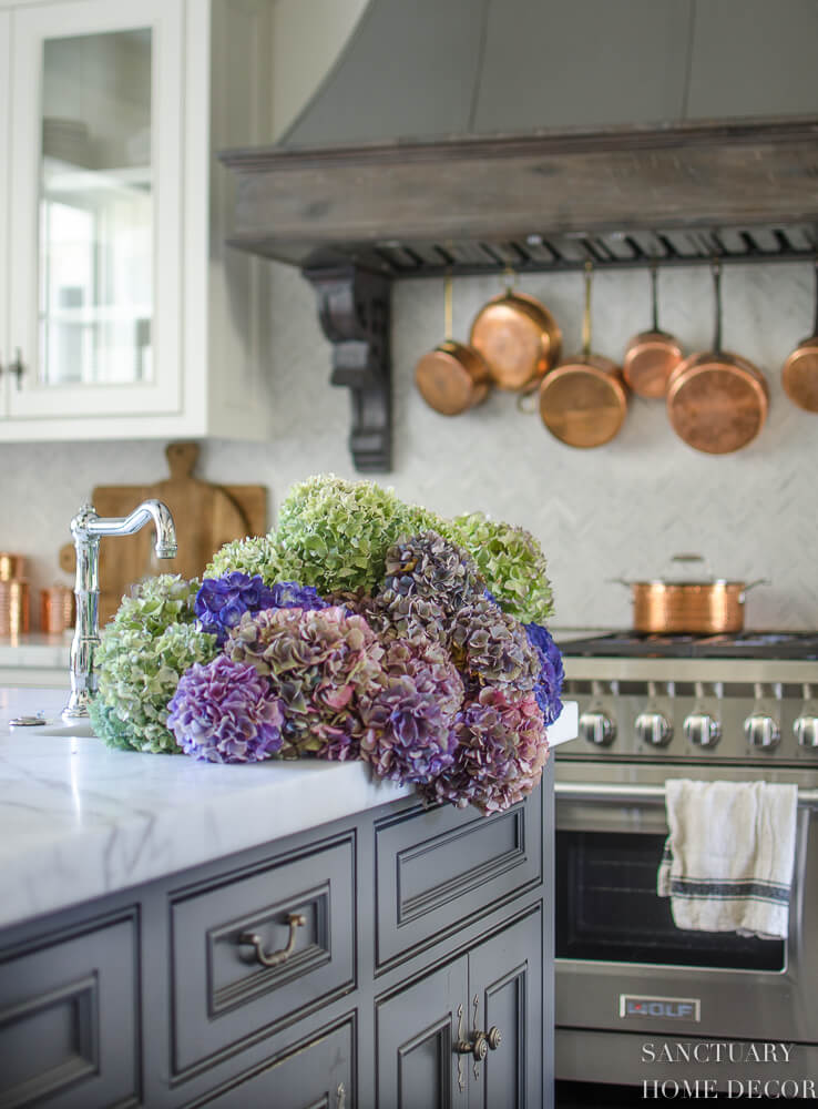 hydrangea bouquet in sink and copper pots on wall