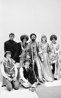 "Tropicalistas no programa Divino Maravilhoso, by Paulo Salomão, 1968  Standing from left to right: Jorge Ben, Caetano Veloso, Gilberto Gil, Rita Lee and Gal Costa. Squatting: Sérgio Dias and Arnaldo Baptista. The tropicalist apogee in 1968 that also resulted in the televising program ""Divino Maravilhoso"" on Tupi TV and lasted until December, before Gil and Caetano - the main tropicalist gurus - being arrested after Christmas"