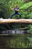 Martial arts black belt practicing blocks on a log over water