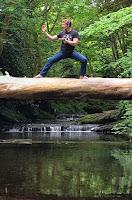 Martial arts black belt practicing blocks on a log over water