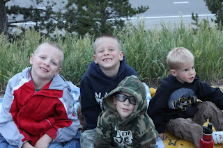 4 boys sitting in the grass