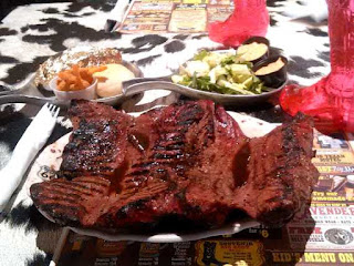 Big Texan 72 oz steak with sides on table