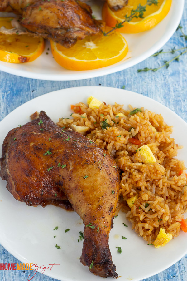 Orange ginger chicken leg quarter with fried rice on a white plate