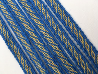 A photograph of a blue and yellow tablet woven band made using the pattern above