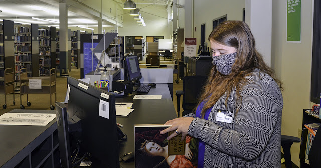 woman stands at library reference desk with a book in her hands