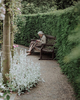 elderly woman seated on a bench in a shaded garden