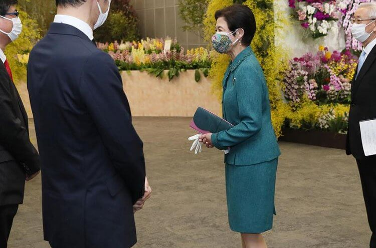 Tokyo Dome City Prism Hall. Japanese orchid flowers of the Ebine variety that bloom in many colors. Green skirt suit, gold earrings
