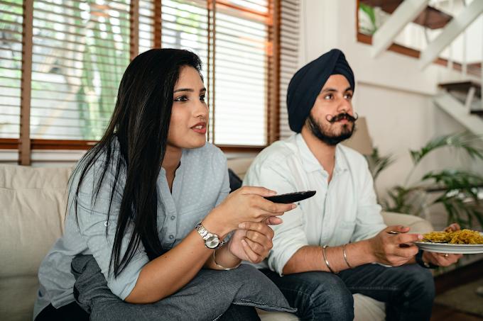 Homem e mulher sentados no mesmo sofá vendo TV. Mulher está com controle na mão enquanto o homem come macarrão