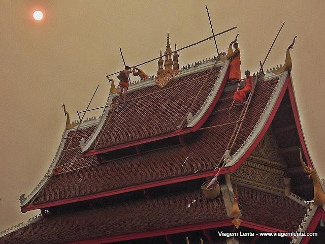 Sem proteções, monges reparam o telhado de um templo em Luang Prabang