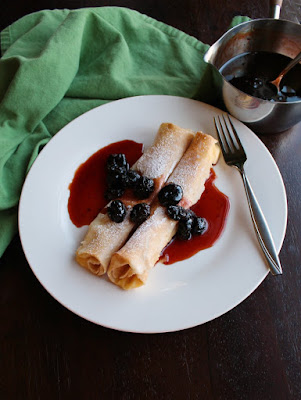 lemon ricotta stuffed crepes on plate with cherry syrup