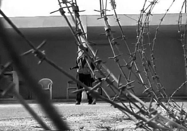 """El cuartel bagdadí de la imagen fue arrebatado por la milicia asiria a los fedayines. El hijo de Sadam, Uday Husein, registró en su interior con una cámara de vídeo las torturas de cientos de prisioneros. Posteriormente, las cintas se comercializaron or todo Irak. El fotograma forma parte del documental """"En busca de los últimos asirios"""". Fotografía por Ferran Barber"""
