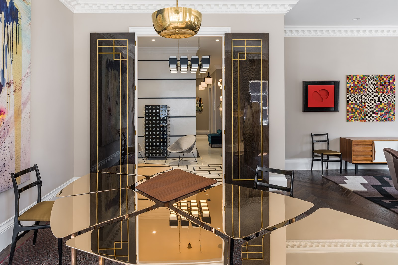 Luxurious eclectic London apartment with pattern geometric rugs, mid century modern furniture and art, dining room