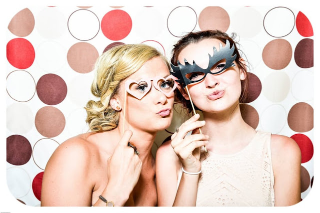 two-woman-taking-photo-in-photobooth-holding-black-and-pink-masquerade-mask