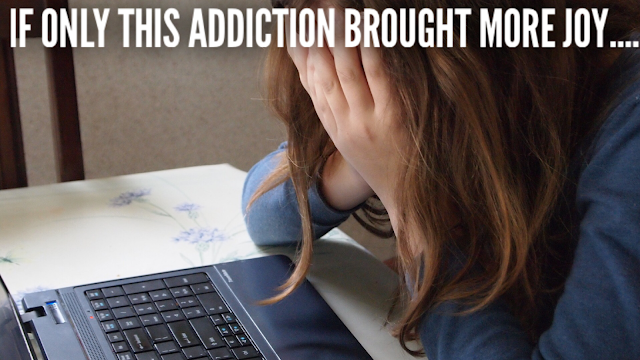 A sad, depressed girl by her laptop.  If only this Facebook addiction brought more joy...