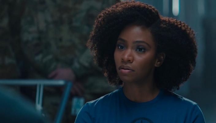 Imagem: a personagem Monica Rambeau, uma mulher negra em um uniforme azul-escuro, olhando para frente na sala de controle da base da E.S.P.A.D.A.