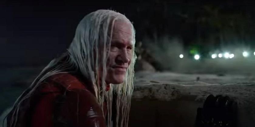 Imagem: o personagem interpretado por Michael Rooker, um homem velho e branco com cabelos loiro platinados e em um traje de couro vermelho, escondido em uma rocha em uma praia.