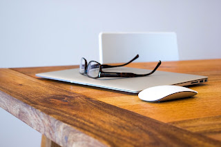 eye glasses sitting on a closed laptop computer