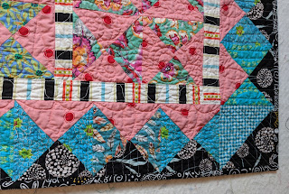 The front corner shows the black and white striped inner border and the outer border of hourglass blocks with pink inside, blue on the sides, and black on the outside. The border has FMQ petals on the pink and  parallel quilting lines elsewhere.
