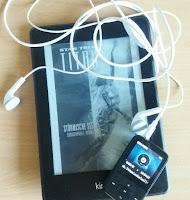 das Bild zeigt einen Kindle mit Titan-Cover und ein Hörbuch