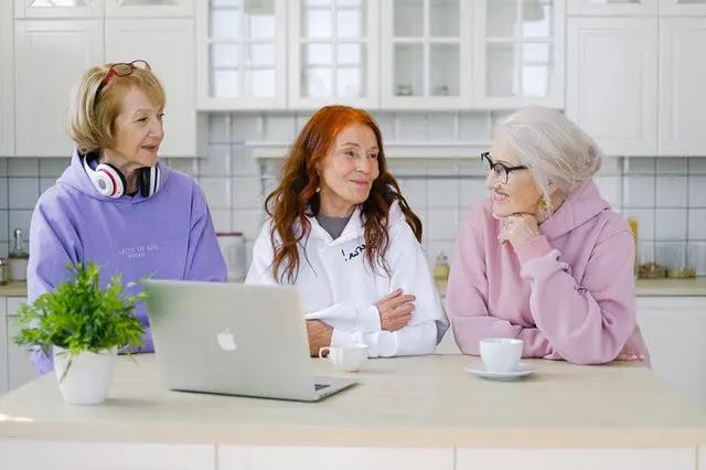 Tres mujeres adultas mayores tomendo café alrededor de una mesa en la cocina frente una laptop