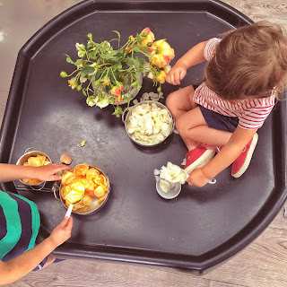children on tuff tray with rose petals and bowls