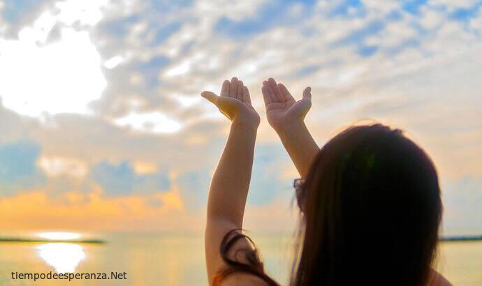 Mujer clamando a Dios con los brazos levantadas