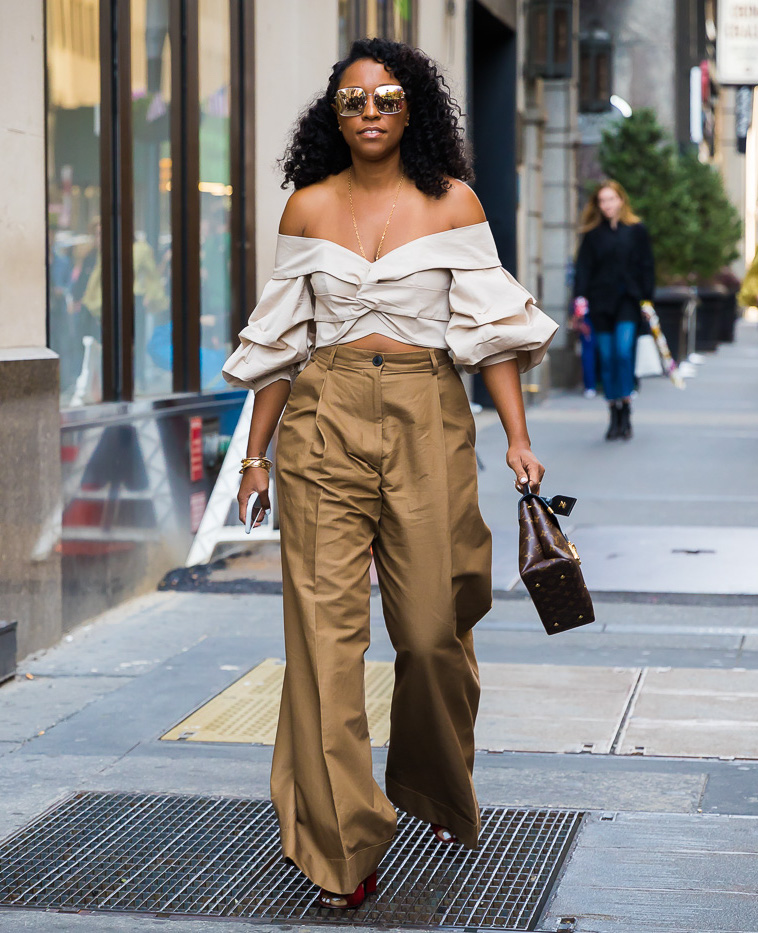 25 Chic Off-the-Shoulder Tops for Sumemr Outfits — Shinoa Turini in a ruffled tan top, Louis Vuitton bag, and tan pants